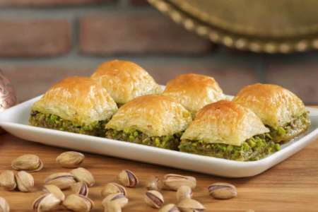 baklava, filo pastry filled with pistachio in golden syrup with pistachio around